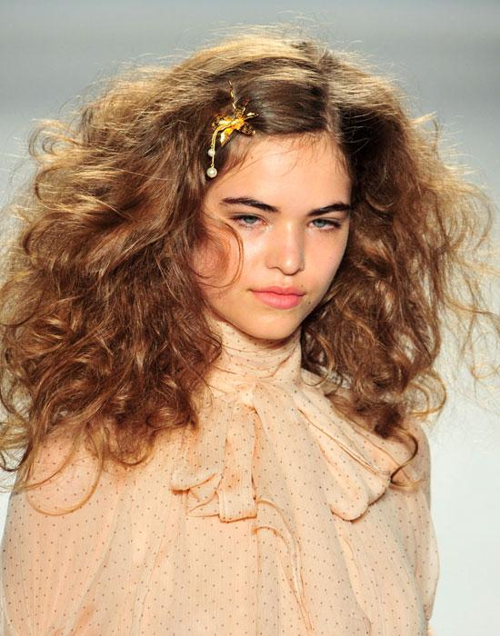 For more of a wild mood, tighten those curls up and add volume with  a strong hairspray (Accessorizing the look with a pin adds a nice touch.